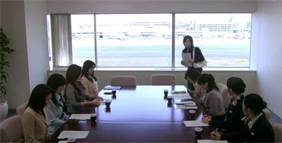 Misaki joins the girls who are assembled at a conference table.