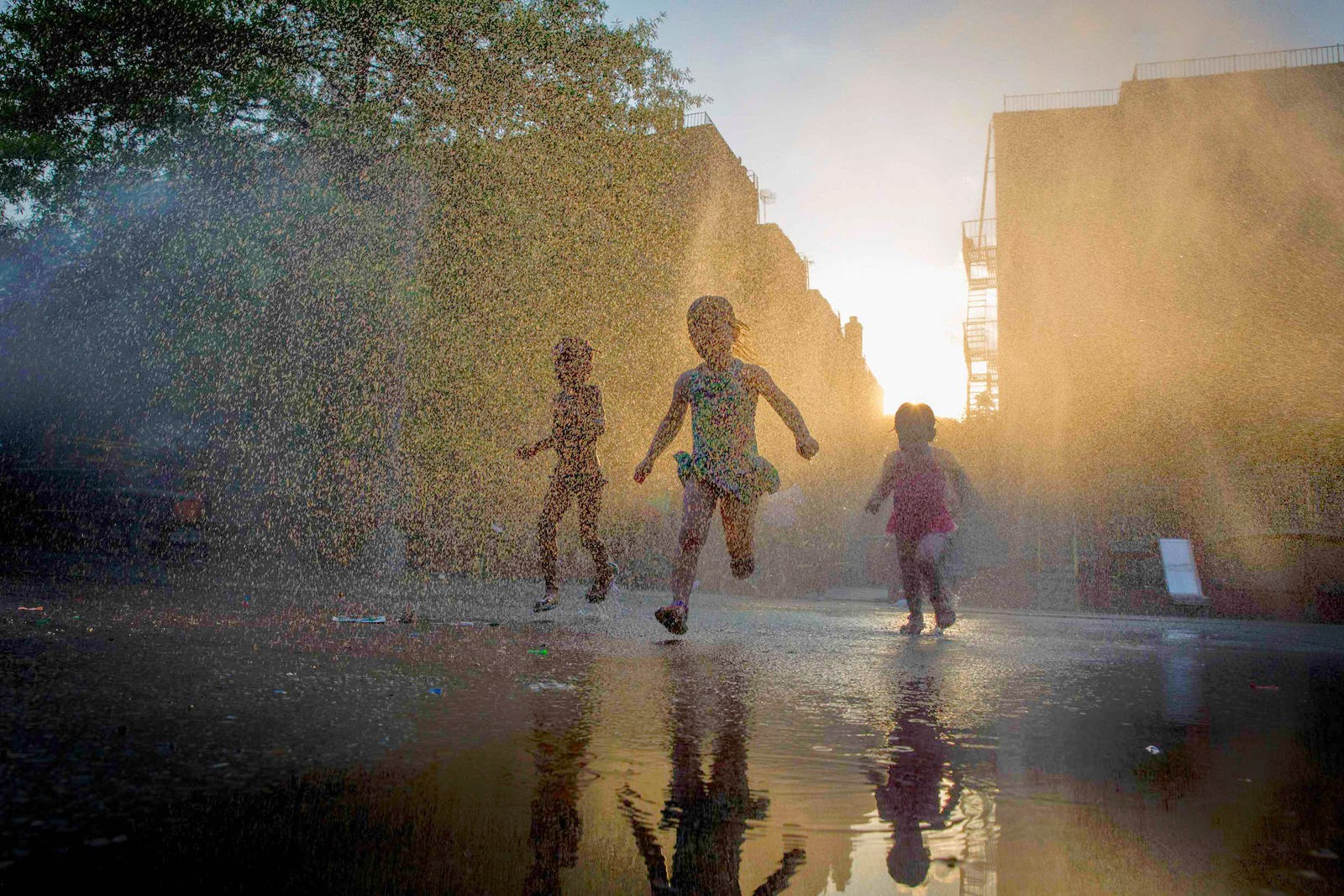 Children play with a sprinkler at a playground in the Park Slope