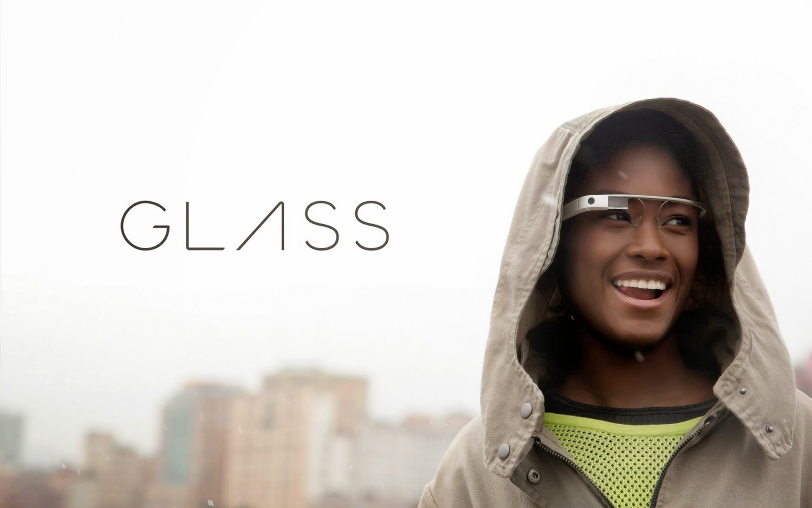 The Google Glass Logo next to a happy Google Glass user.  A metropolitan city is in the background.