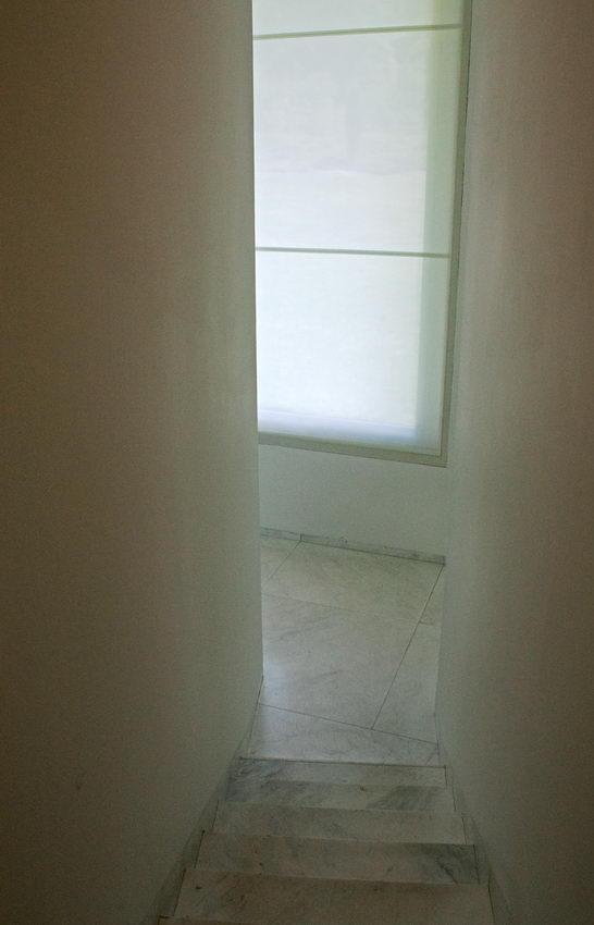 Apontamento fotográfico sobre uma janela com cortinas translúcidas, ao fundo da escadaria de um corredor