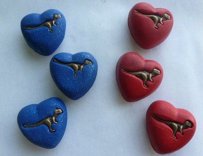 red and blue heart-shaped magnets with a dinosaur in the center of each