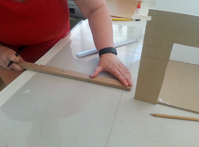 Person measuring a piece of perspex.