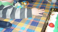 Miúdo com a mão esticada para roubar um morango do bolo