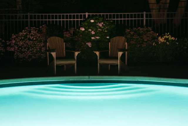 swimming pool and Adirondack chairs at night