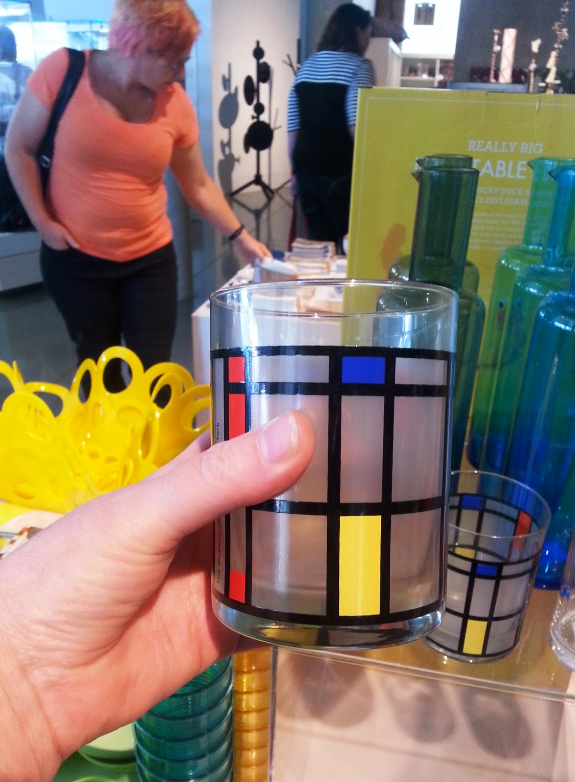 A hand holding a Piet Mondrian-styled glass in a gift shop.