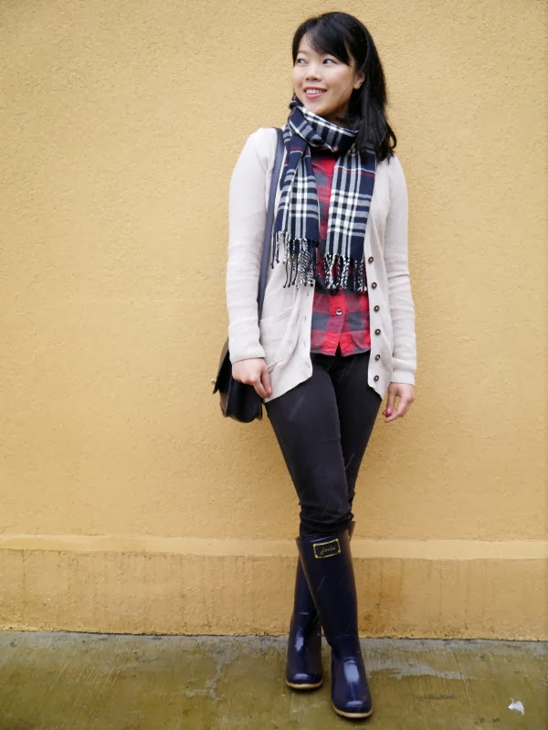 Cozy layers: Plaid scarf and buffalo plaid shirt, black skinny jeans, long oatmeal cardigan, navy blue wellies and shoulder bag.