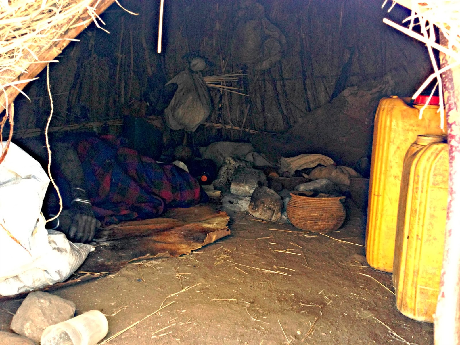 Old Mursi woman seeks refuge from the sun inside her hut