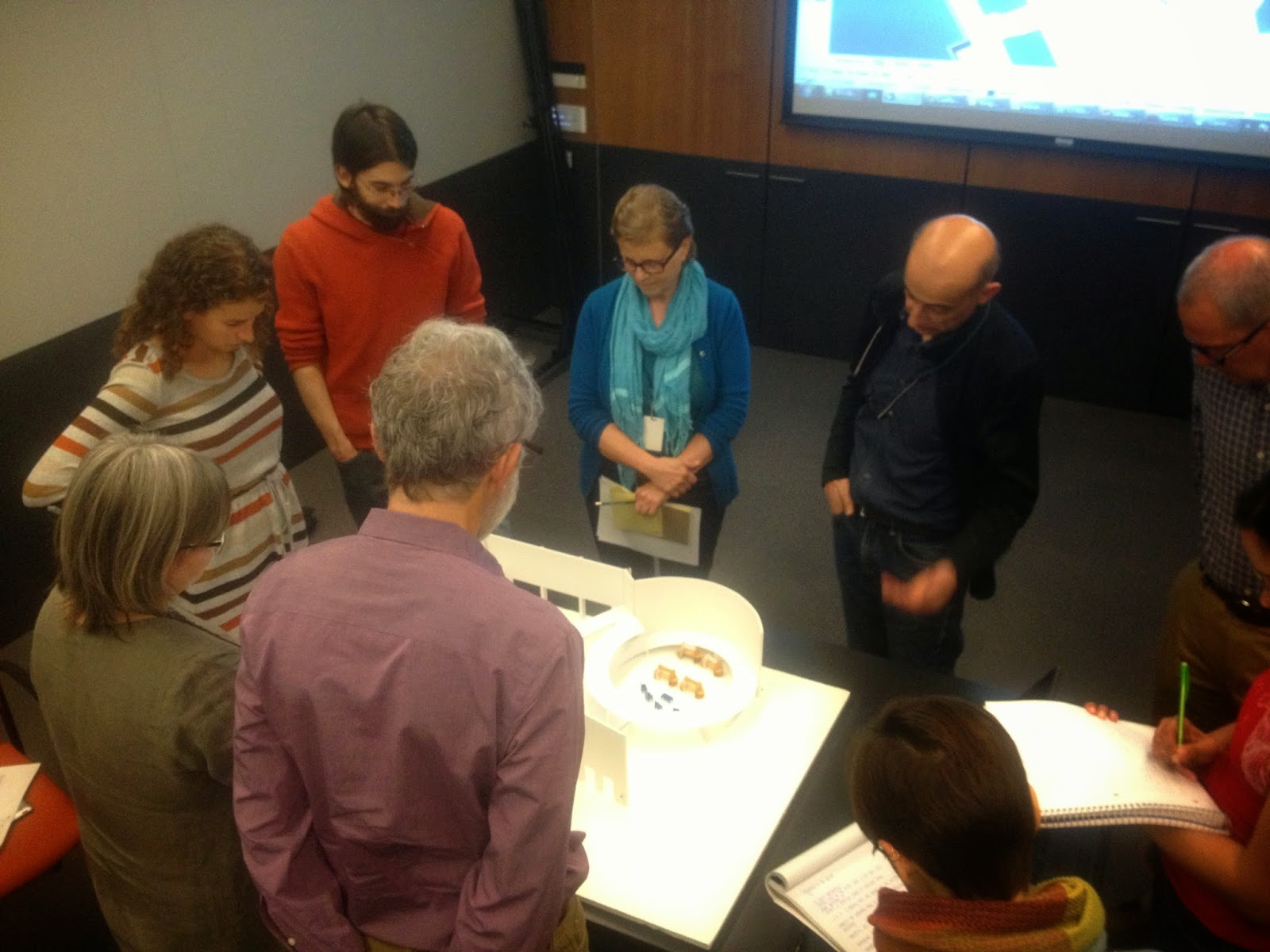 A foam core model is sitting on a table as Board Members gather around to evaluate and discuss the plan with Longmore institute staff members.