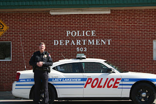 Chief Stapleton in front of a Lacy Lakeview Police car.