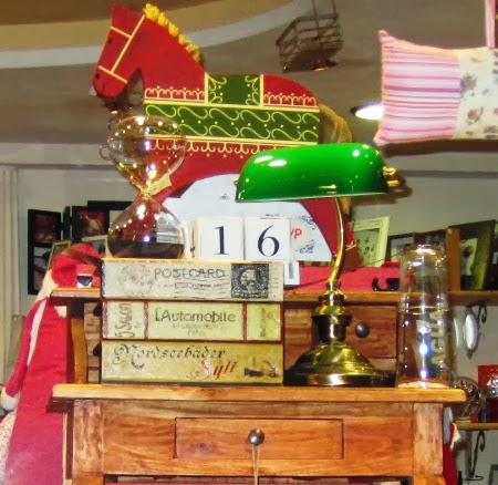 Lámpara verde de escritorio. Libros cajas. Calendario.