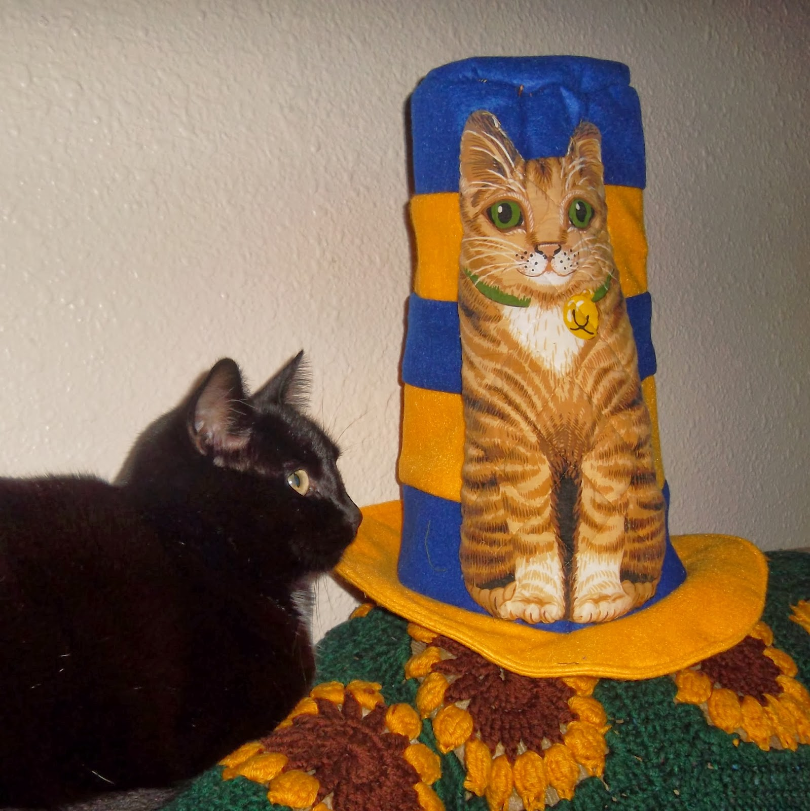 To the left, my black cat Starfire, shown in profile, faces a blue-and-gold striped 'Cat in the Hat' felt hat with a fabric-printed and quilted brown tabby cat appliqued onto it.