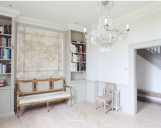 Foyer with herringbone wood floor, crystal chandelier, a bench and built in bookshelves