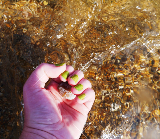 Hand Holding Pebble in the Sea