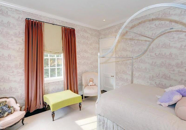 Girl's room with a canopy bed, toile wallpaper, yellow bench window seat and coral floor length curtains