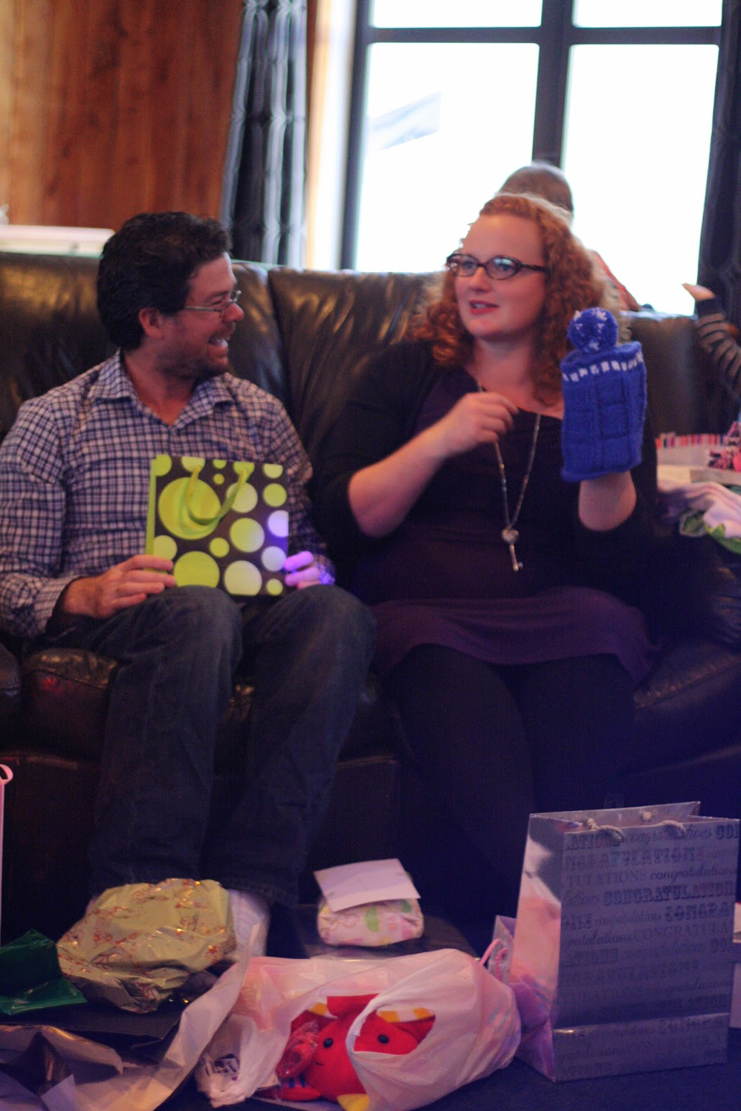 Jenn and Zac opening gifts, smiling.
