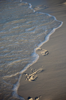 Waves washing away footprints in the shore along Pensacola Beach, FL