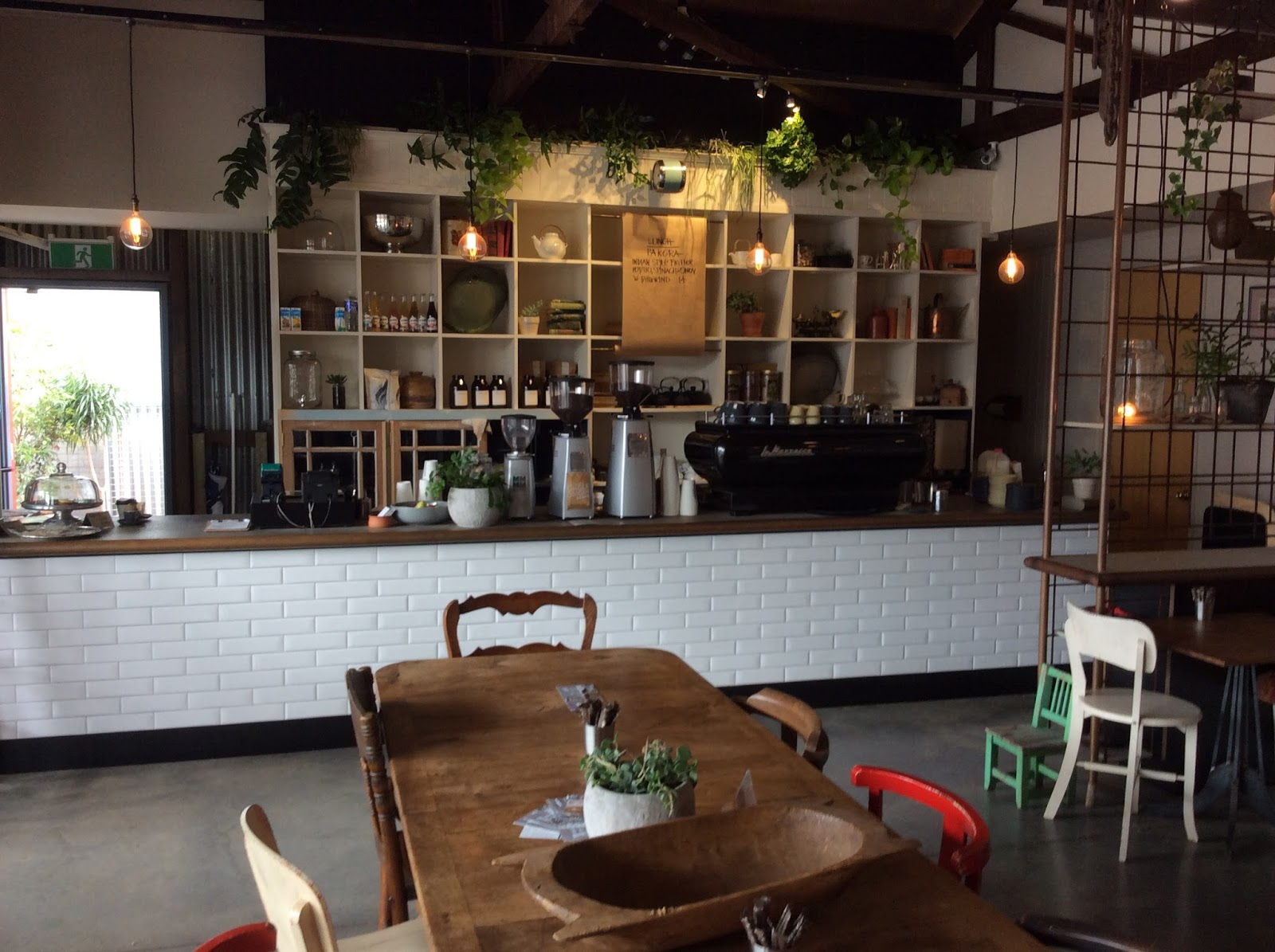 inside the eclectic mix of tables and chairs against the simple counter and shelves really make you feel at home the plants spilling over the shelves - Glass Front Cafe 2015