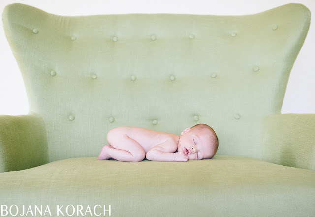 newborn baby boy photographed sleeping on a green chair