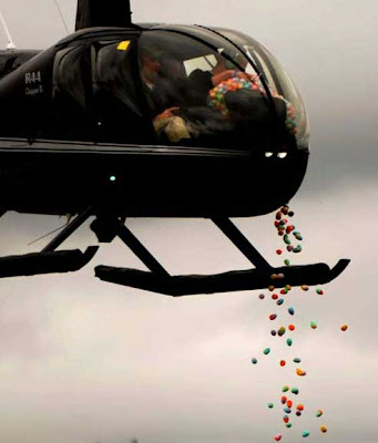 Black helicopter with people inside dropping colorful plastic eggs into the air below