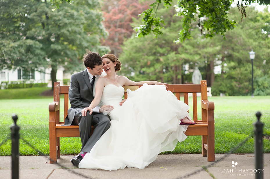 Bride sitting with groom on a bench and laughing at Boston College