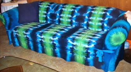 Long couch with blue and green tie-dyed slipcover