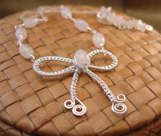 Sterling silver wire woven bow pendant adorned with rose quartz beads created by Vicky Brown of Shore Debris
