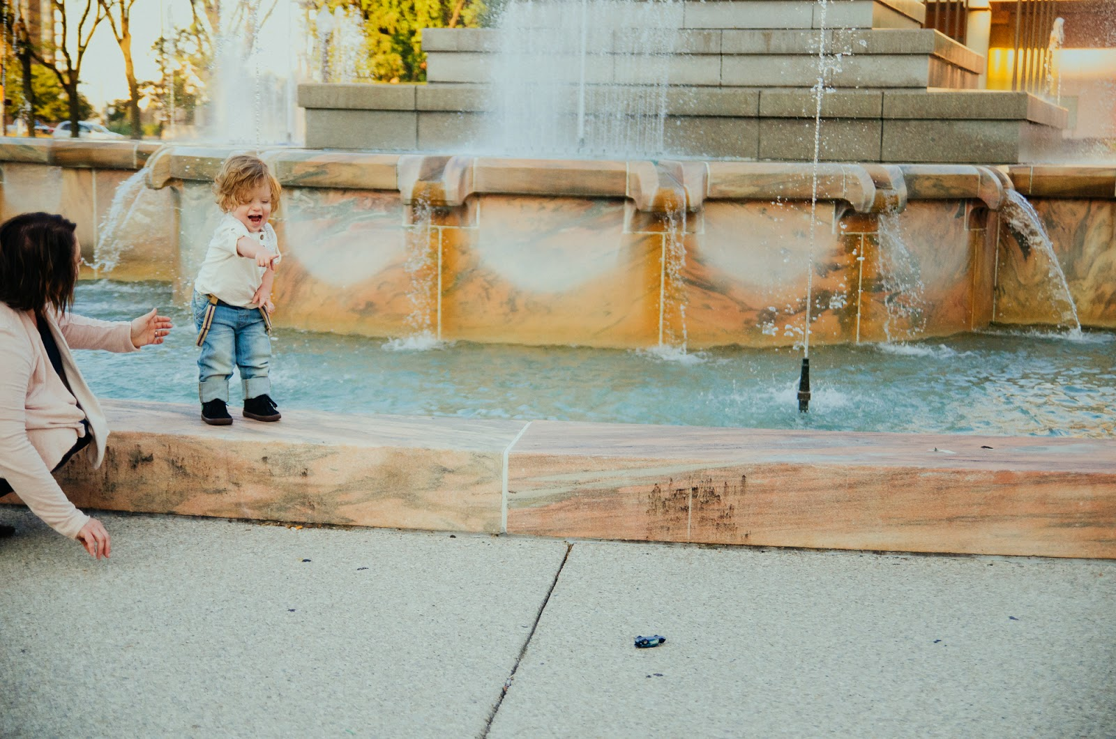 mom plays with her son at a fountain, indianapolis family photographer