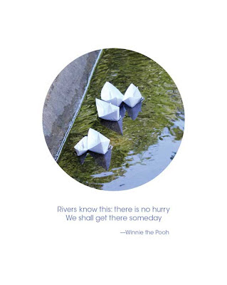 paper boats sailing down a street with quote