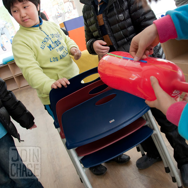 Students making a balloon rocket at Winter English Camp at Bibong Elementary in Ochang, South Korea.