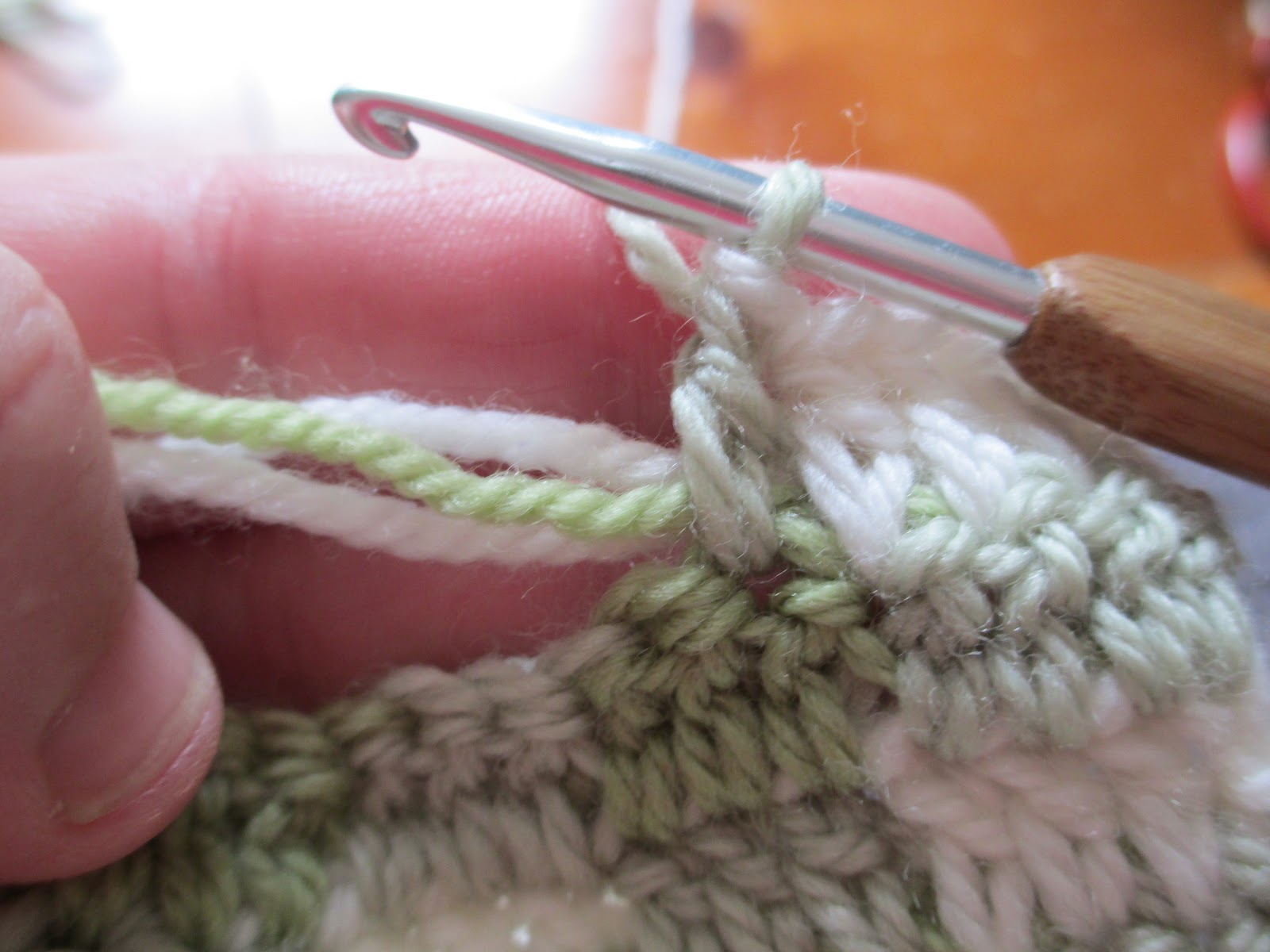 ... crochet the next stitches over the remaining ends and the cream yarn