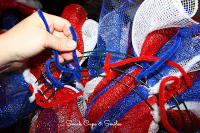 tying on the mesh ribbon rolls to the wreath frame