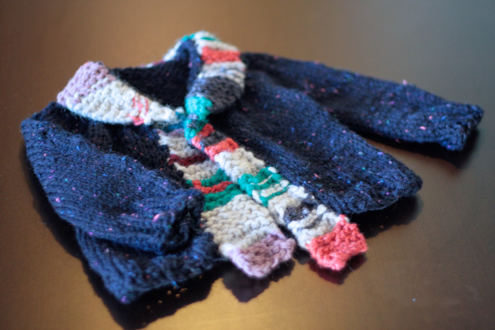 A little blue hand knit baby jumper, with a colourful striped button band.