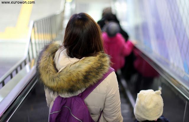 Mujer y niña bajando las escaleras mecánicas del metro de Seúl