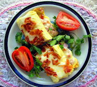 A breakfast of rolled omelette, greens and tomato.