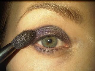 applying purple eyeshadow to lids
