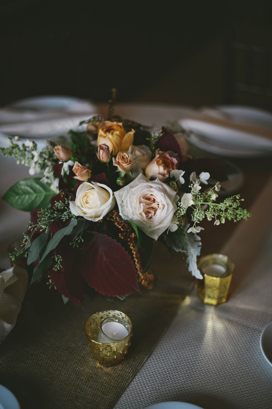 les fleurs : barn at gibbet hill : gold mercury votive cups around glass compote arrangements filled with rich greenery, soft blue greens, caramel, yellow and ivory : burlap table runner : late summer barn wedding
