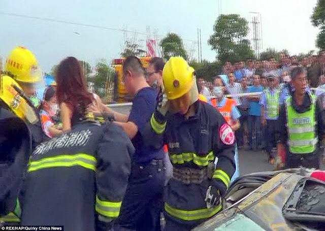Astounded: Bystanders look on as the unidentified woman is pulled out alive