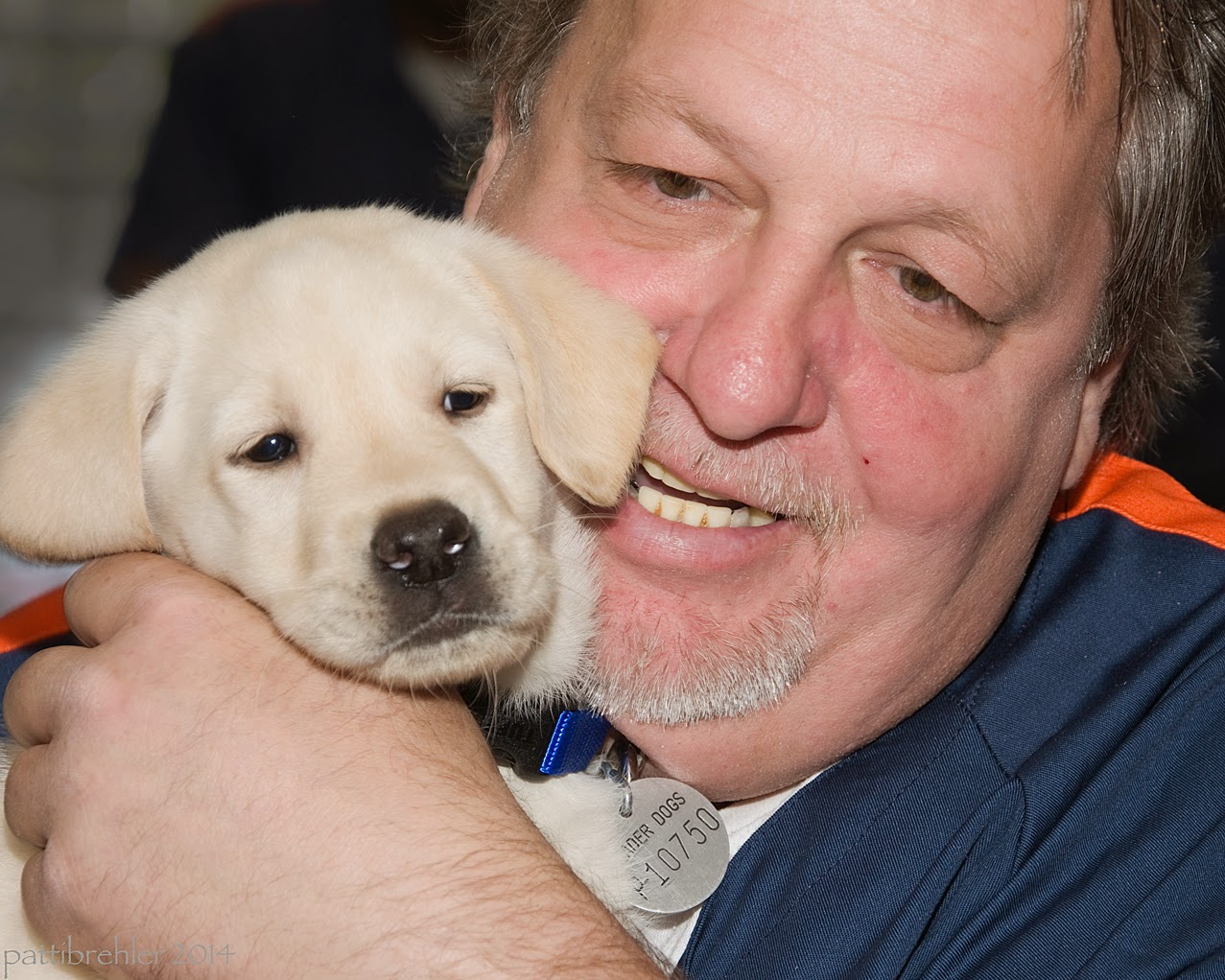 A close up shot of a man's face pressed next to the head of a small yellow lab puppy. The man is wearing a blue prison shirt, he is smiling and holding the puppy with his left hand. The puppy is facing forward.