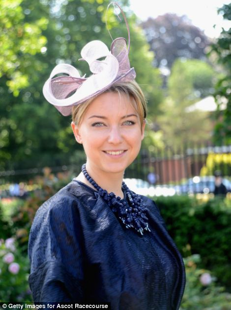 a lady in navy with a small lilac fascinator inspired hat on day 5 of Royal Ascot 2014