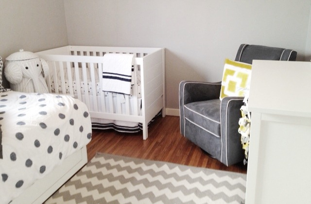 nursery with a white crib, glider upholstered gray armchair with white piping, and a yellow pillow