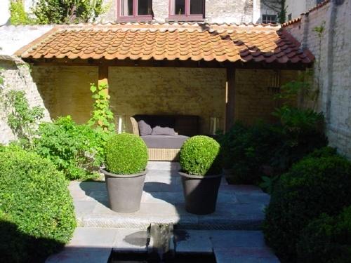 diferenca entre quintal e jardim:Um telheiro no meio do verde, as bolas de buxo talhado fazem a