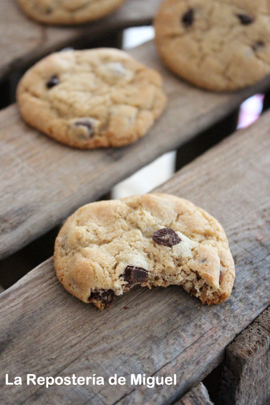Una galleta  con un bocado encima de una caja de madera es la protagonista de la foto, detras de aprecian varias galletas mas.