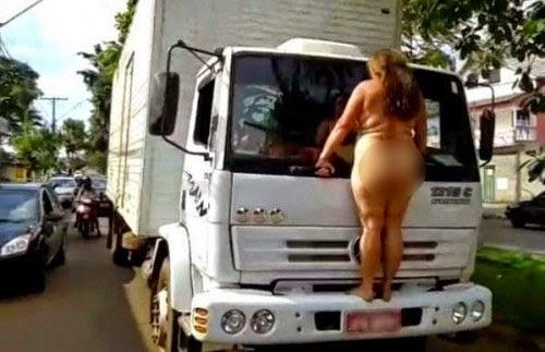 Mulher nua sobe em para-choque de caminhão e para o trânsito.