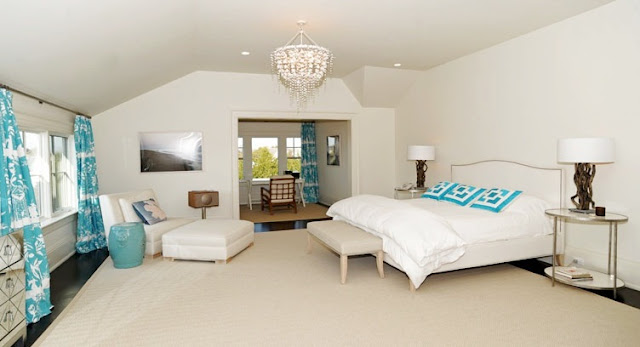 master bedroom with white walls, upholstered headboard, dark wood floor, turquoise curtains and a shell chandelier