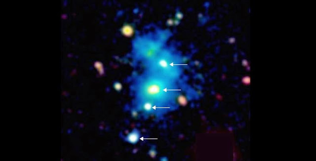Image of the region of the space occupied by the rare quasar quartet. The four quasars are indicated by arrows. The quasars are embedded in a giant nebula of cool dense gas visible in the image as a blue haze. The nebula has an extent of one million light-years across, and these objects are so distant that their light has taken nearly 10 billion years to reach telescopes on Earth. This false color image is based on observations with the Keck 10m telescope on the summit of Maunakea in Hawaii. Image: Arrigoni-Battaia & Hennawi / MPIA