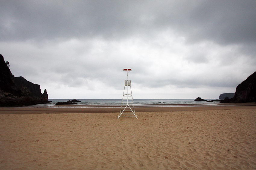 Paisagem da praia deserta com o posto de vigia do nadador-salvador em primeiro plano e centrado na imagem