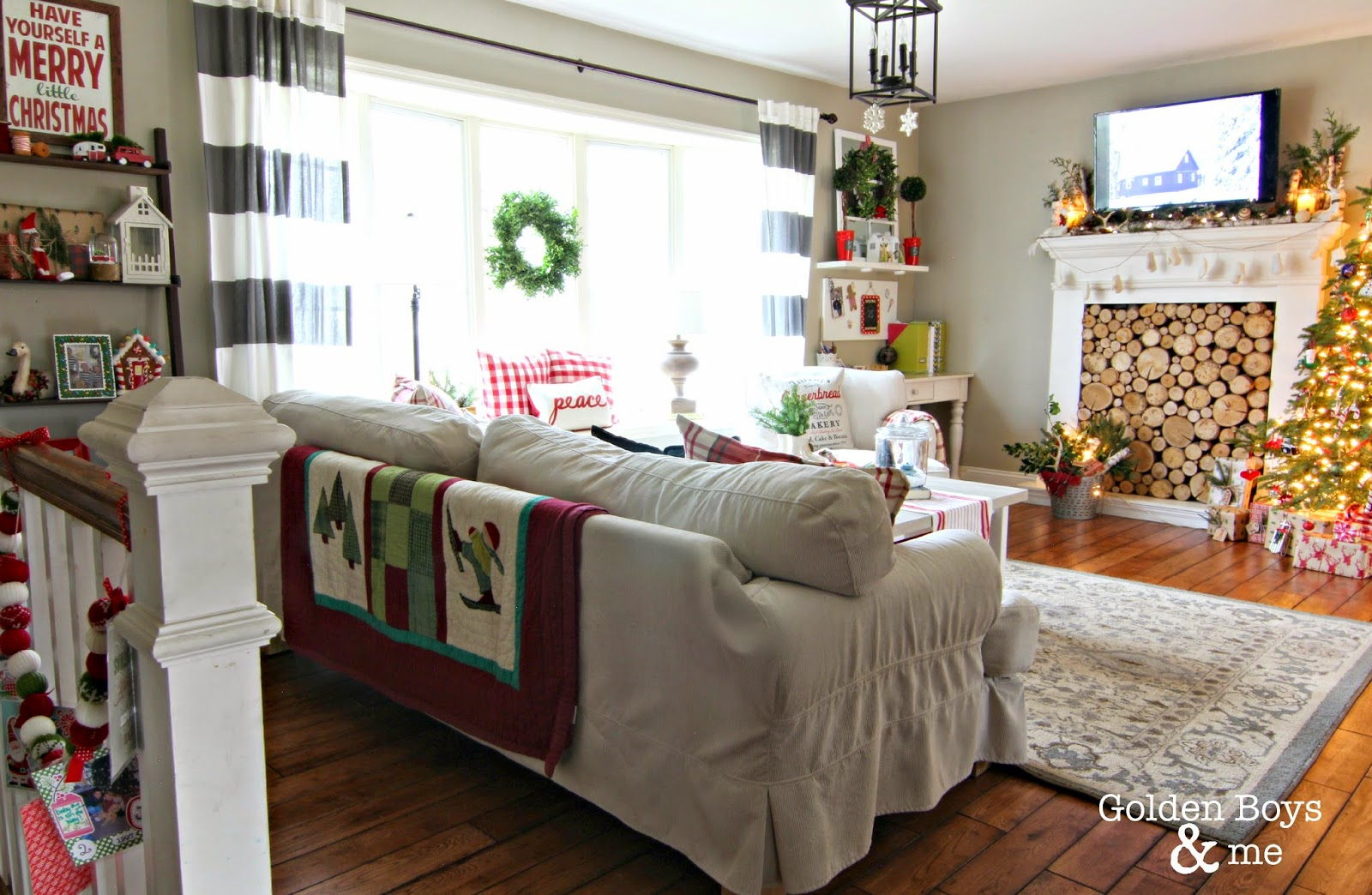 Casual living room with striped drapes and Ikea slipcovered furniture with faux fireplace and Christmas decor-www.goldenboysandme.com