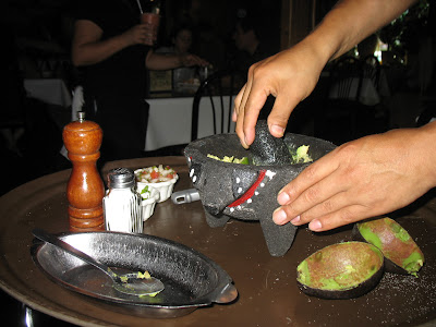 The waiter making us fresh guacamole in the Molcajete