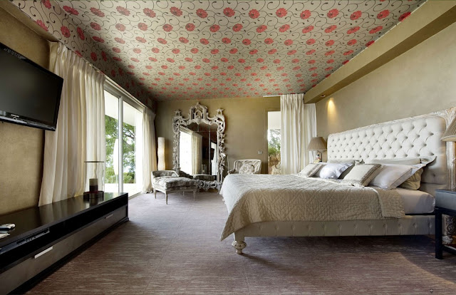 Large luxury master bedroom with king size bed and red flowers on the ceiling