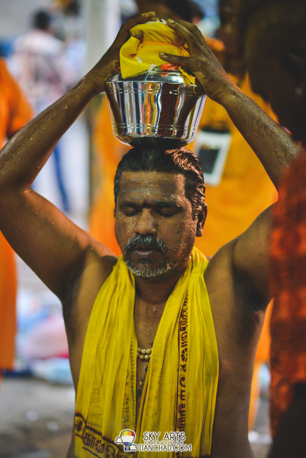 A man after shower receiving blessing before carry the barrel of milk uphill to Batu Caves